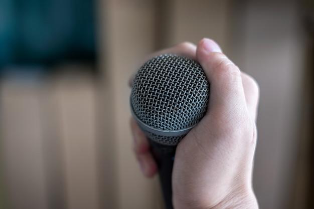 Hand, die ein mikrofon auf unschärfe hält