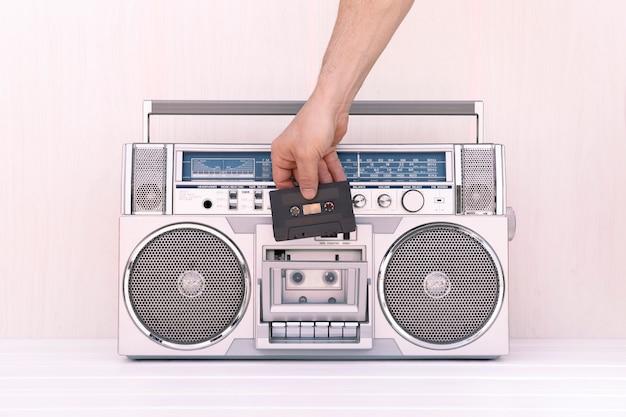 Hand, die ein musikband in das deck einer vintage-radiokassette einlegt