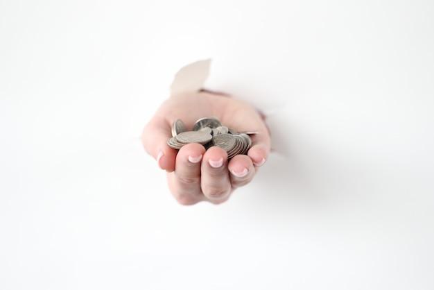 Hand, die ein paar münzen aus zerrissenem papier herauszieht