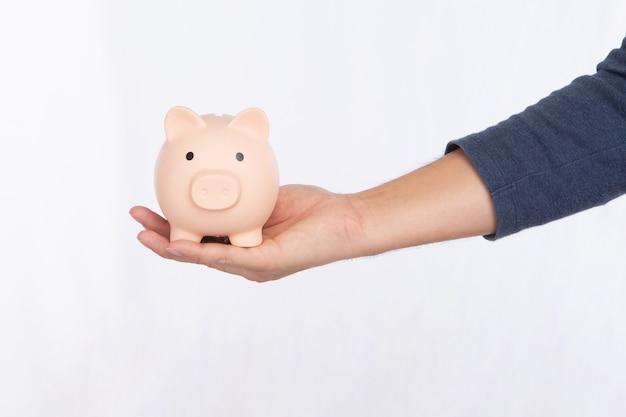 Hand, die ein rosa sparschwein lokalisiert auf weißem hintergrund hält