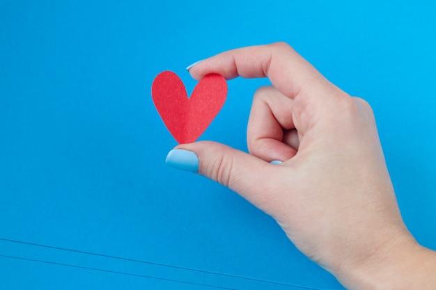 Hand, die ein rotes herz auf einem blauen hintergrund hält. hintergrund für den valentinstag