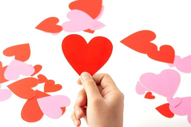 Hand, die ein rotes herzförmiges papierhandwerk isoliert hält, rotes und rosa herzförmiges papierhandwerk sind verstreut, konzeptliebe und valentinstag.