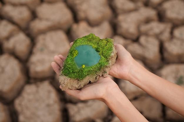 Hand, die ein stück rissige erde hält, die einen grünen baum und einen blauen teich hat