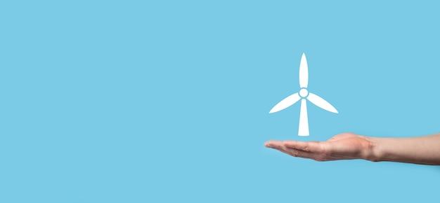 Hand, die ein symbol einer windmühle hält, die umweltenergie auf blauem hintergrund produziert.