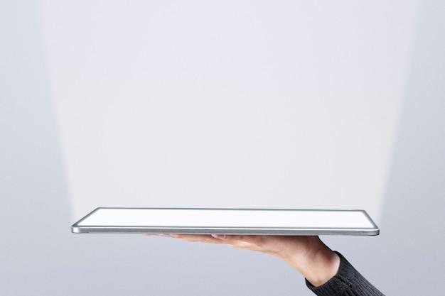 Hand, die ein unsichtbares hologramm präsentiert, das von der fortschrittlichen technologie des tablets projiziert wird