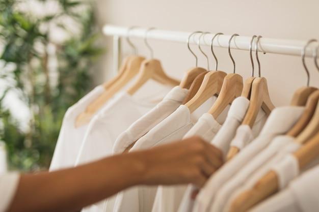 Hand, die ein weißes hemd von der garderobe wählt