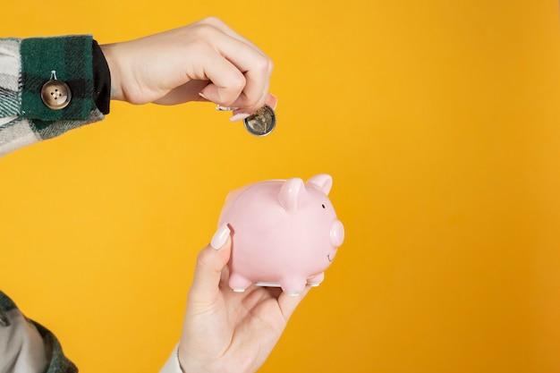 Hand, die eine 2-euro-münze in ein sparschwein legt