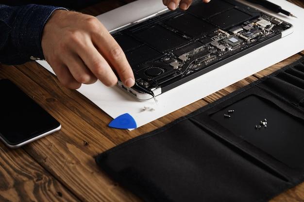 Hand, die eine abgewinkelte esd-pinzette verwendet, um staub von den elektronischen platinen eines kaputten, schlanken computer-laptops zu entfernen, um ihn zu reparieren und wieder zum laufen zu bringen.