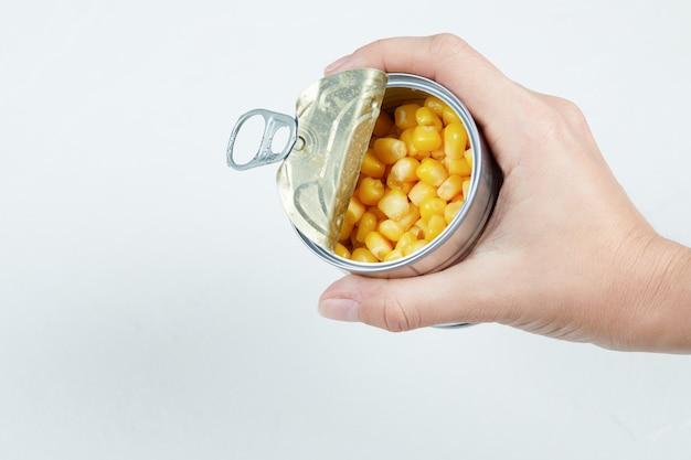 Hand, die eine blechdose gekochten zuckermais hält.