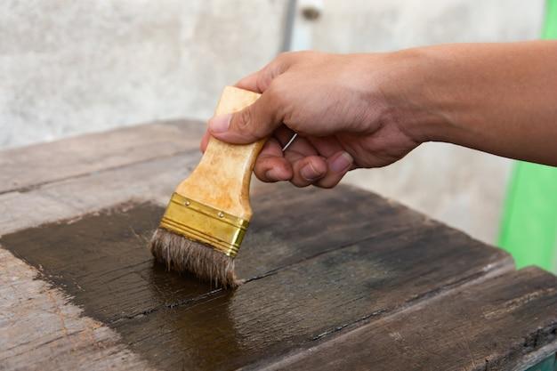 Hand, die eine bürste hält malende hölzerne bauholzbretter tauchen mit hölzernem fleck auf
