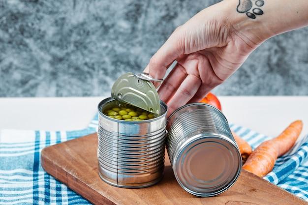 Hand, die eine dose gekochte grüne erbsen auf einem weißen tisch mit gemüse und tischdecke hält.