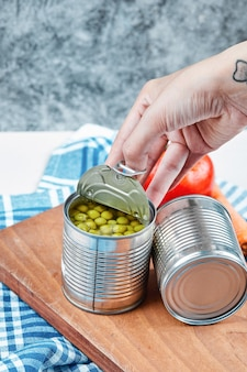 Hand, die eine dose gekochte grüne erbsen auf einem weißen tisch mit gemüse und tischdecke hält. Kostenlose Fotos
