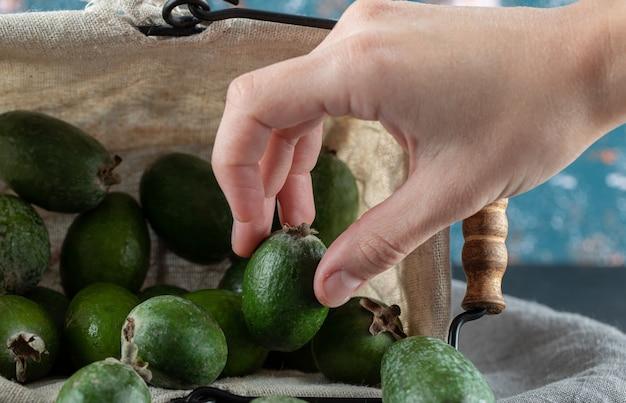 Hand, die eine feijoa aus dem korb auf einer grauen tischdecke nimmt
