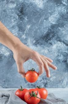 Hand, die eine frische ganze tomate an einer grauen wand nimmt.
