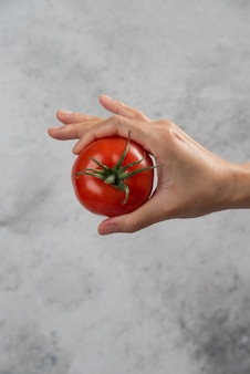 Hand, die eine frische rote tomate auf einem marmorhintergrund hält.