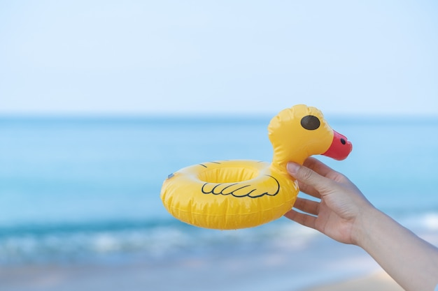 Hand, die eine gelbe ente am strand mit einem meer im hintergrund hält.