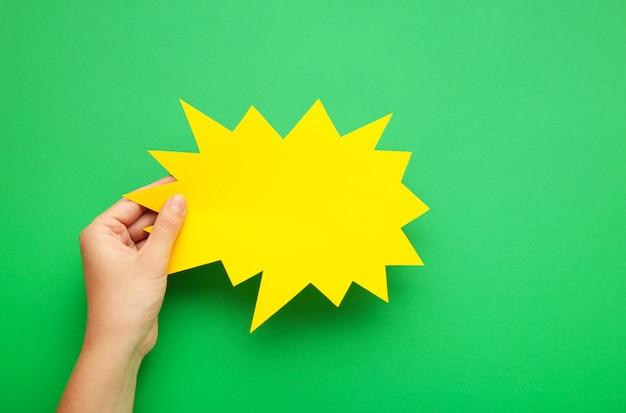 Hand, die eine gelbe leere sprechblase auf grün hält