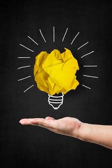 Hand, die eine glühbirne mit einer papierkugel