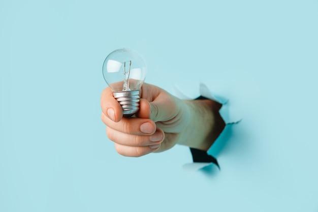 Hand, die eine glühbirne von einem zerrissenen loch im blauen hintergrund hält. konzept der energieeinsparung.