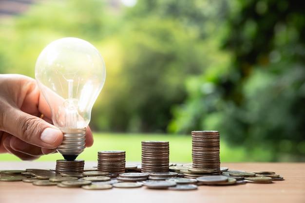 Hand, die eine glühlampe mit münzenstapel hält.