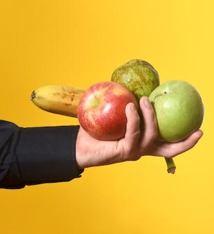 Hand, die eine gruppe von früchten auf gelbem hintergrund hält