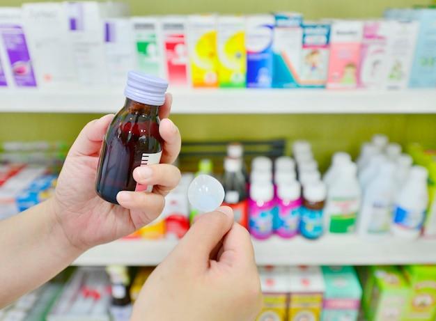 Hand, die eine hustensaftflasche in der apotheke hält
