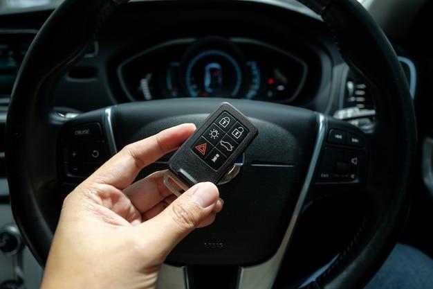 Hand, die eine intelligente schlüssellose direktübertragung des autos auf fahrersitzposition hält.