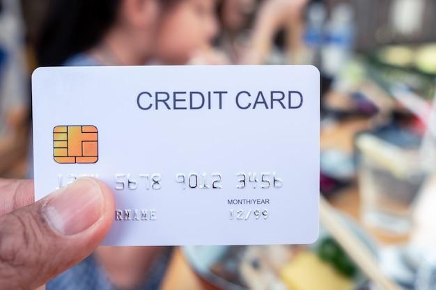 Hand, die eine kreditkarte im restaurant hält
