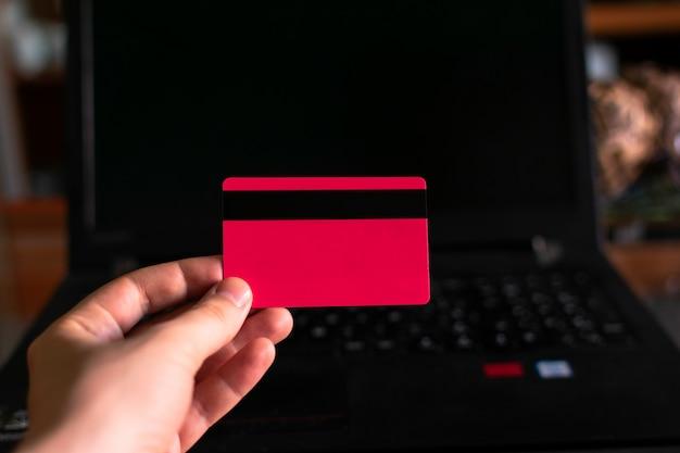 Hand, die eine kreditkarte mit einem laptop hält