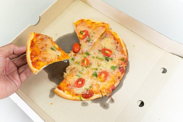Hand, die eine läuse von pizza-mittag- oder abendessen-krustenfleisch-belagsoße mit grünem pfeffer aufhebt - traditionelles schnellimbiß in peper brettkasten geöffnet.