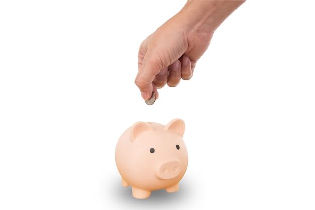 Hand, die eine münze hält, um in das rosa sparschwein, lokalisiert auf weißem hintergrund, sparkonzept zu setzen