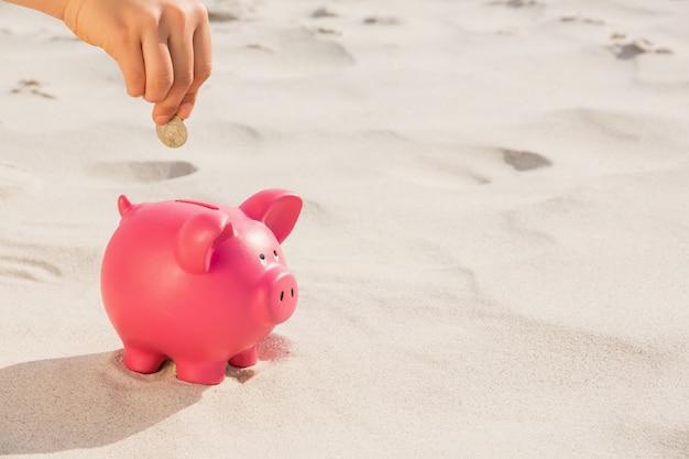 Hand, die eine münze in das sparschwein