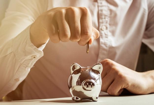 Hand, die eine münze in sparschwein legt