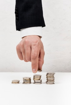 Hand, die eine münze von einem stapel nimmt