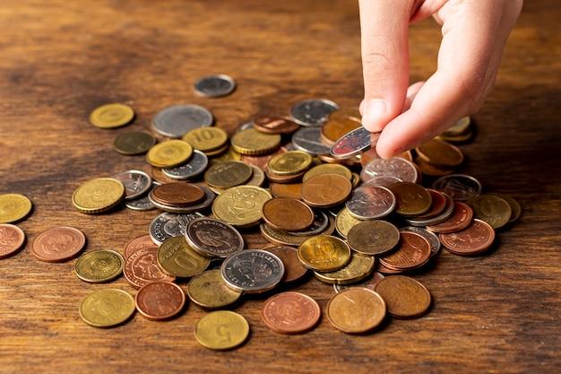 Hand, die eine münze von einer hohen ansicht des stapels hält