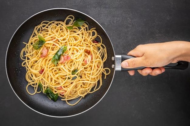 Hand, die eine pfanne mit spaghetti-nudeln mit getrocknetem chili, knoblauch, süßem basilikum und speck auf dunklem texturhintergrund hält, draufsicht