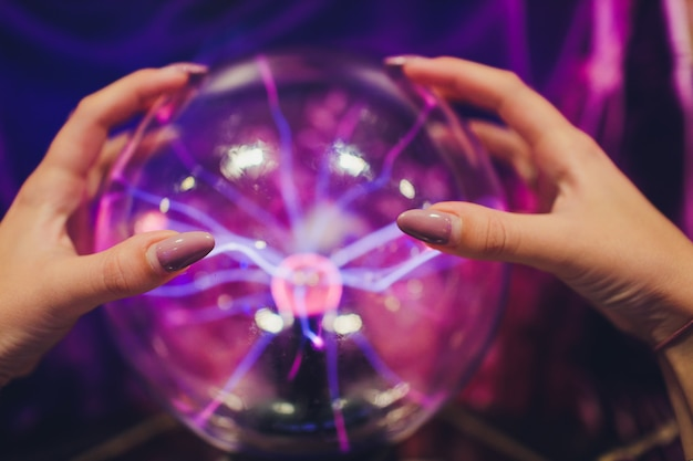 Hand, die eine plasmakugel mit glatten magentablauen flammen berührt.