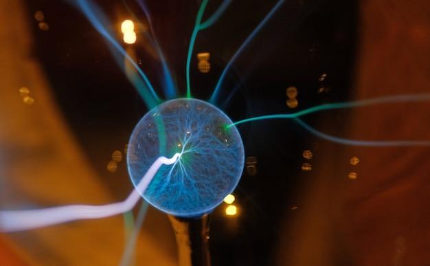 Hand, die eine plasmakugel mit glatten magentablauen flammen berührt