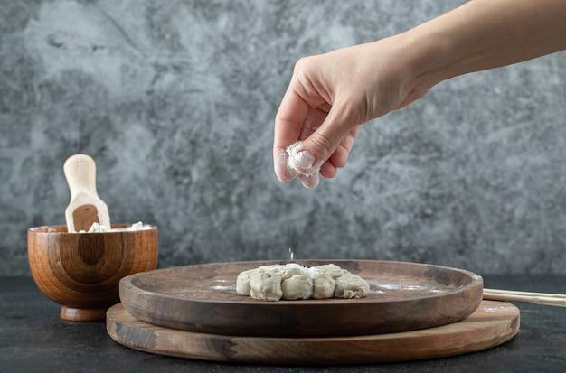 Hand, die eine prise mehl von einer holzschale auf grau nimmt.