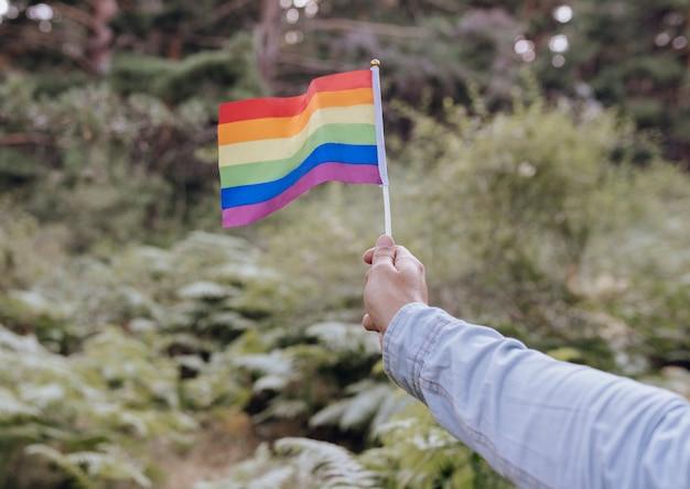 Hand, die eine regenbogenfarbene lgbt-flagge hält