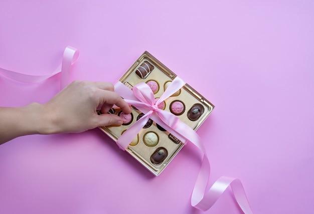 Hand, die eine schokolade von der schachtel der pralinen mit rosa schleife auf rosa hintergrund nimmt