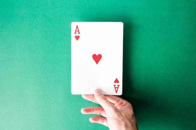 Hand, die eine spielkarte auf grünem hintergrund hält.
