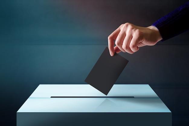 Hand, die eine stimmzettel-karte in den abstimmungs-kasten fallenläßt