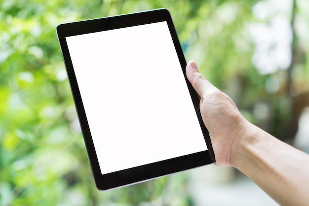 Hand, die eine tablette mit leerem bildschirm auf grünem unschärfehintergrund hält