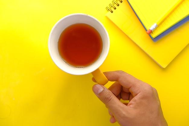 Hand, die eine tasse grünen tee auf gelb hält