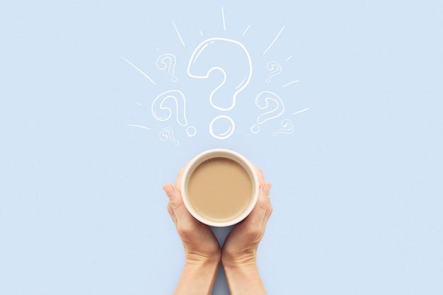 Hand, die eine tasse mit heißem kaffee auf einem blauen hintergrund hält. fragezeichen. frühstückskonzept mit kaffee oder tee. guten morgen, nacht, schlaflosigkeit. flache lage, draufsicht