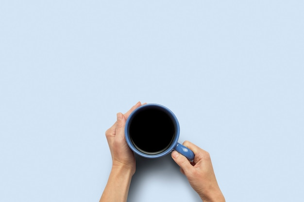 Hand, die eine tasse mit heißem kaffee auf einem blauen hintergrund hält. frühstückskonzept mit kaffee oder tee. guten morgen, nacht, schlaflosigkeit. flache lage, draufsicht