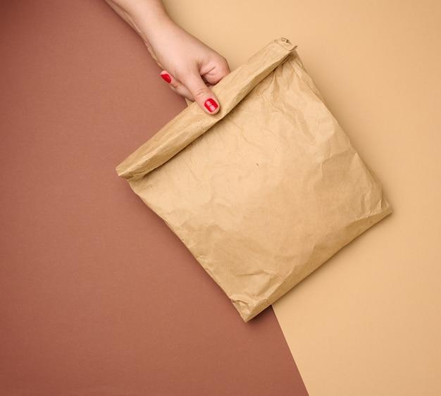 Hand, die eine volle papiertüte aus braunem kraftpapier auf braunem hintergrund hält, nahaufnahme