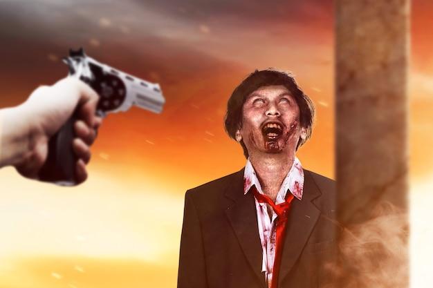 Hand, die eine waffe auf einen zombie zeigt. halloween-konzept
