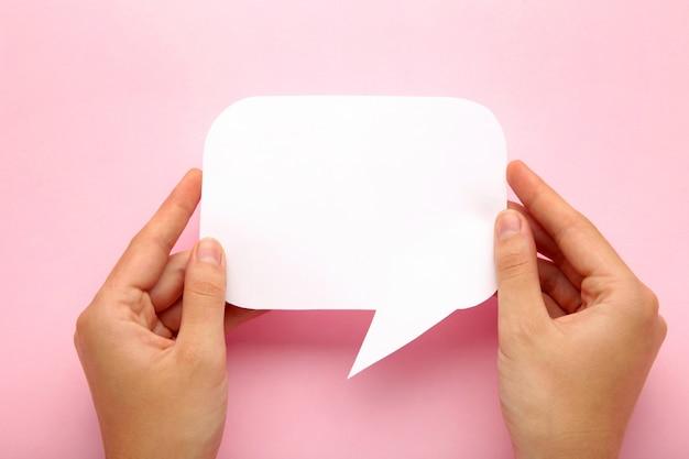 Hand, die eine weiße leere sprachblase auf rosa hintergrund hält